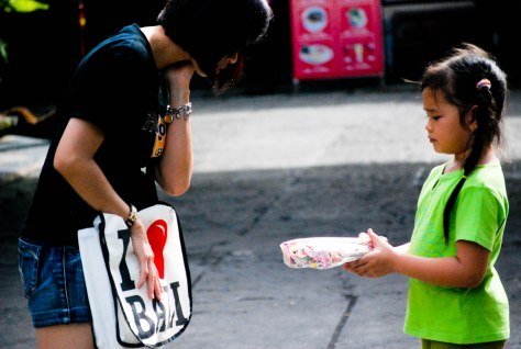 Little girl selling stuffs in order to earn some money